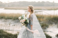 bride in blue wedding dress with bouquet on a dock