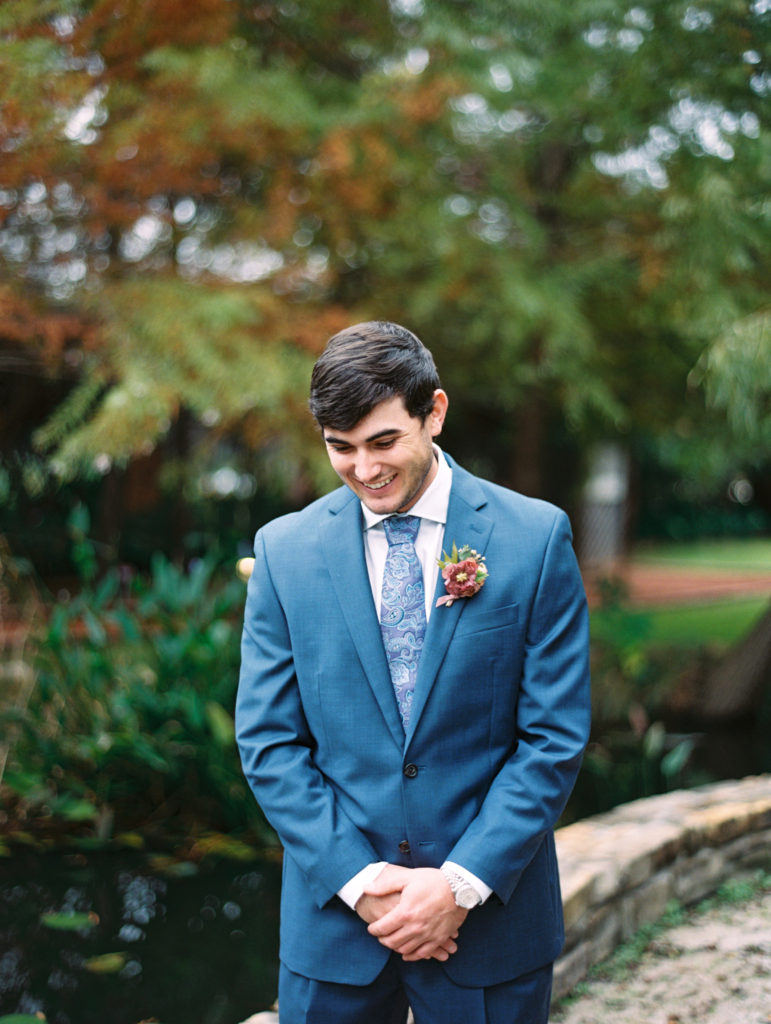 Groom in a blue suit with mauve boutonniere