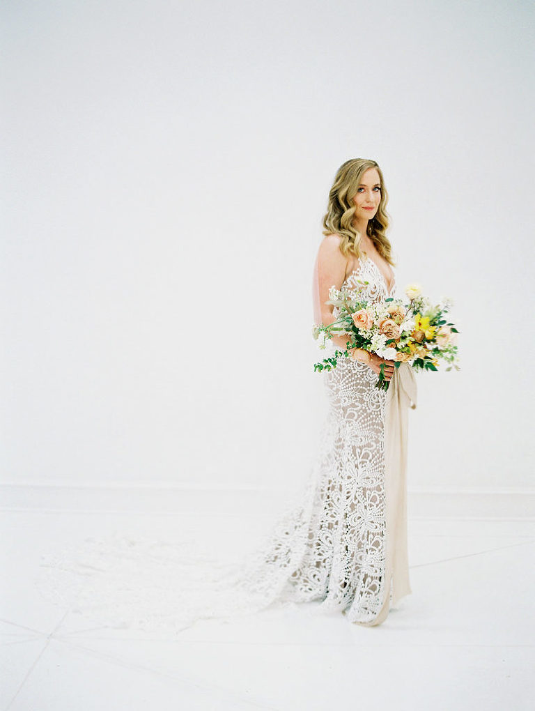 Made With Love Sasha wedding dress worn by Charla Storey Photography for her own bridal portraits featuring a peach and yellow bouquet. Wedding planned and designed by Birds of a Feather Events